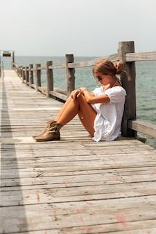 Mujer pensativa sentado en un muelle