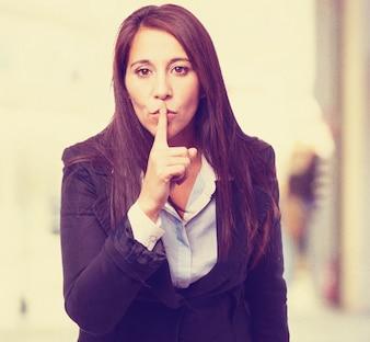 Mujer pidiendo silencio con un dedo en los labios