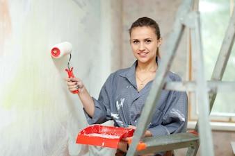 Mujer pinta la pared en casa