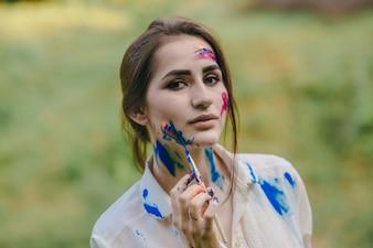 Mujer pintándose la mejilla de azul con un pincel