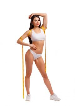 Mujer posando con una cinta métrica liada en su cuerpo