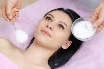 Mujer profesional aplicando crema en la cara a otra mujer