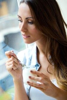 Mujer que come el yogur cerca de la ventana
