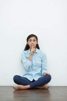 Mujer que hace gesto del silencio y se sienta en suelo
