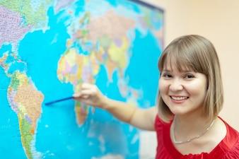 Mujer que muestra algo en el mapa del mundo