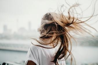 Mujer que mueve la cabeza y el pelo en el aire.
