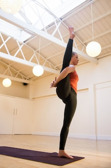 Mujer que realiza ave del paraíso pose de yoga en la estera del ejercicio