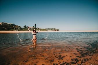 Mujer que salpica hacia fuera el agua con las manos en la playa en Australia.