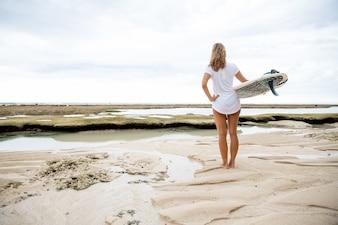Mujer que se coloca en orilla de mar con la tabla hawaiana