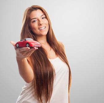 Mujer que sostiene el coche de juguete.