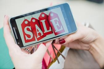 Mujer que sostiene el smartphone con la inscripción en la pantalla
