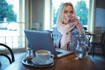 Mujer que tiene un vaso de agua durante el uso de ordenador portátil