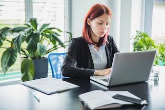 Mujer que trabaja con la computadora portátil en oficina moderna