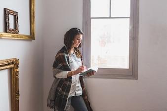 Mujer relajada escribiendo junto a la ventana