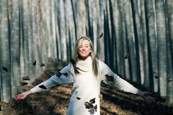 Mujer relajada jugando con las hojas en el parque