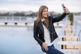 Mujer riendo apoyada en una barandilla haciéndose una autofoto