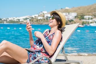 Mujer riendo mientras mira un teléfono inteligente