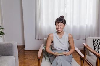 Mujer riéndo sentada en silla