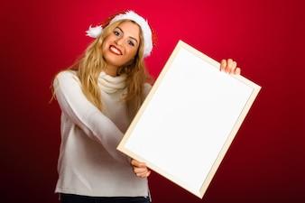 Mujer rubia con el sombrero de santa que sostiene el tablero blanco