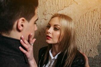 Mujer rubia tocando y mirando la cara de un hombre