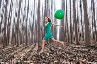 Mujer saltando con un globo verde en el bosque