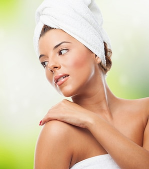 Mujer sensual con la toalla en la cabeza de la mano en el hombro