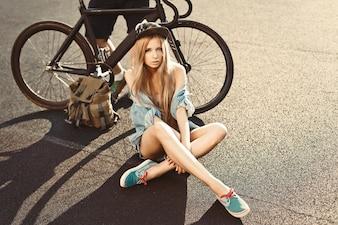 Mujer sensual sentada en el suelo con bicicleta de fondo