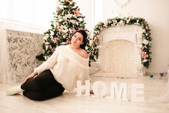 Mujer sentada en el suelo con un árbol de navidad
