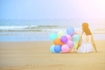 Mujer sentada en la arena junto a un montón de globos