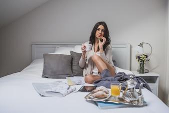 Mujer sentada en la cama con una fresa en la mano