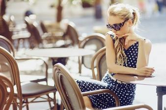 Mujer sentada en un restaurante mirando al suelo