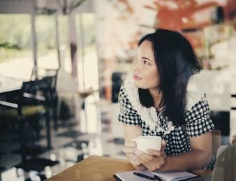 Mujer sentada en una cafetería