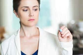 Mujer seria escribiendo sobre la placa de vidrio con marcador