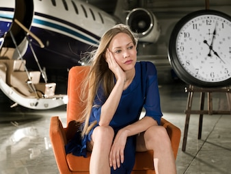 Mujer sería sentada en un aeropuerto con un reloj al lado