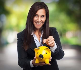 Mujer sonriendo con traje y echando una moneda a una hucha