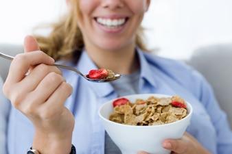 Mujer sonriendo con un bol de cereales