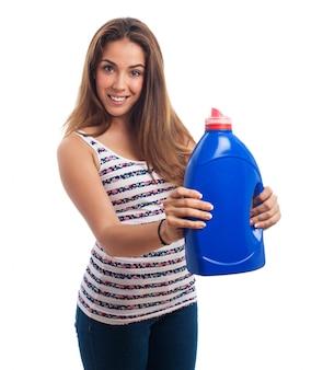 Mujer sonriendo con un bote de detergente azul