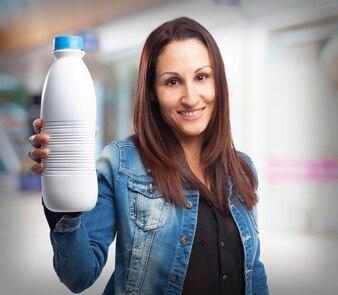 Mujer sonriendo con una botella de leche
