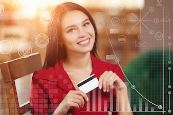 Mujer sonriendo con una tarjeta de crédito