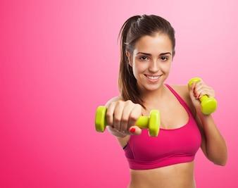 Mujer sonriendo mientras da un puñetazo con pesas en las manos