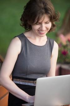 Mujer sonriendo mientras escribe en el portátil