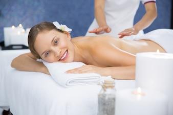 Mujer sonriendo mientras le dan un masaje en la espalda