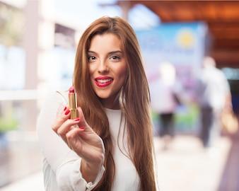 Mujer sonriendo mientras sujeta un pintalabios
