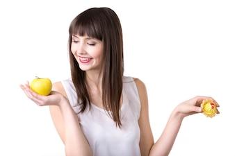 Mujer sonriendo mirando una manzana