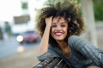 Mujer sonriendo posando con la cabeza sobre el respaldo del banco de madera