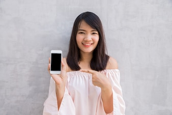 Mujer sonriendo señalando su móvil