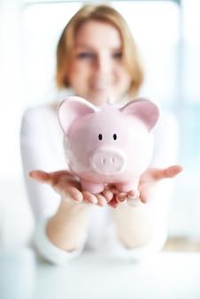 Mujer sonriente ahorra dinero en la hucha