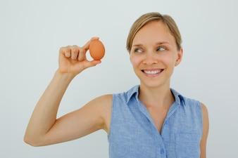 Mujer sonriente celebración de huevo con dos dedos