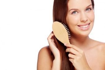 Mujer sonriente cepillándose su pelo sano