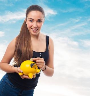 Mujer sonriente echando una moneda a una hucha de cerdo